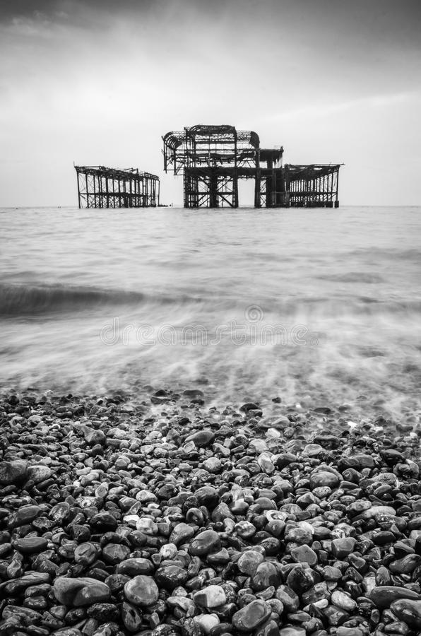 A black and white of the old burnt out pier in Brighton. A long shutter speed creating this really magical effect on the water of this black and white image of royalty free stock image