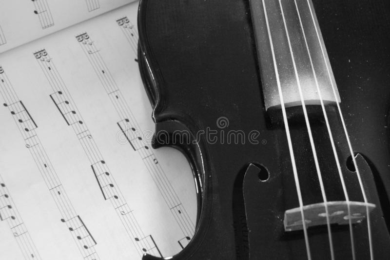Black and White of Orchestra instrument laying on music paper. Orchestra string instrument viola or violin laying on music paper in black and white royalty free stock images