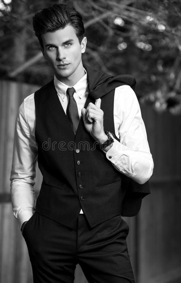 Free Black-white Outdoor Portrait Of Elegant Handsome Man In Classical Vest Near Wooden Fence Royalty Free Stock Photos - 80768748