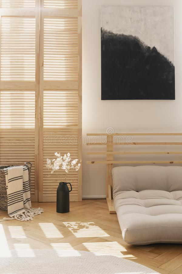 Black and white painting above beige scandinavian bed made of futon in natural bedroom interior, real photo with mockup on the stock photography
