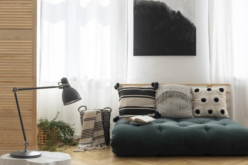 Black and white painting above scandinavian futon with pillows in trendy living room interior, real photo with mockup on the empty royalty free stock images