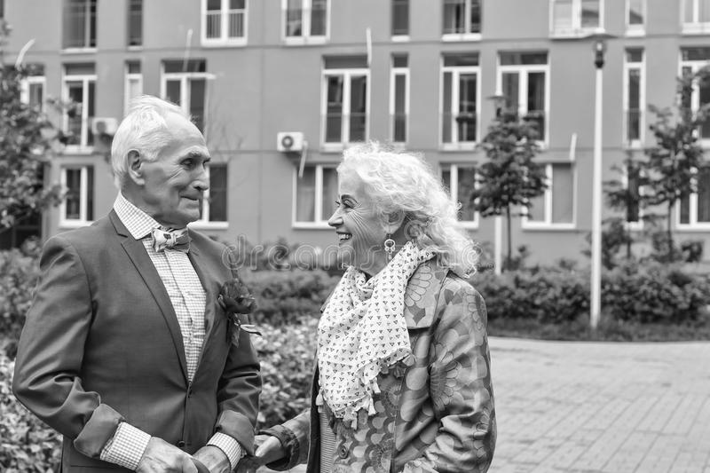 Black and white.age, cheerful, joyful, lifestyle, love, 60s, pensioner, people,. Black and white. pair of elderly handsome people on a walk in a modern city stock image