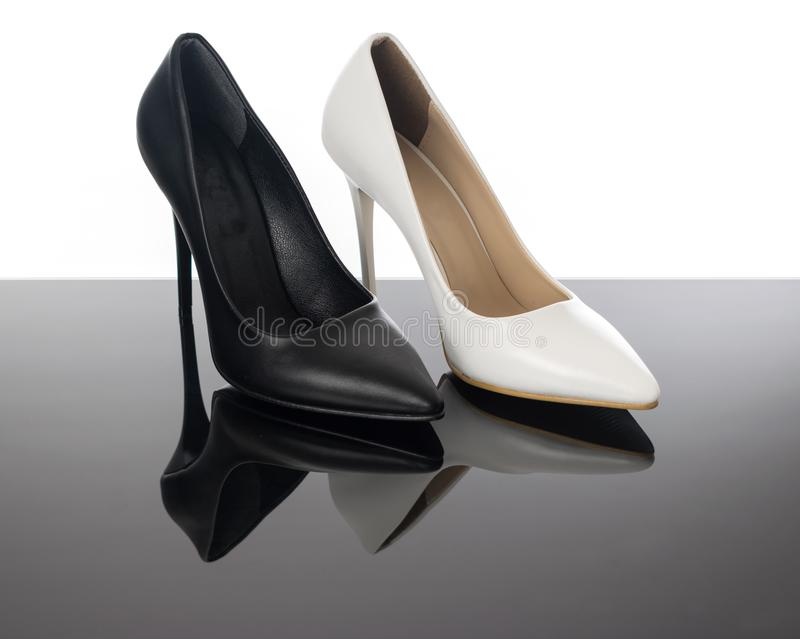 Black and white high heels pointed woman stiletto shoes on reflective floor. stock photography
