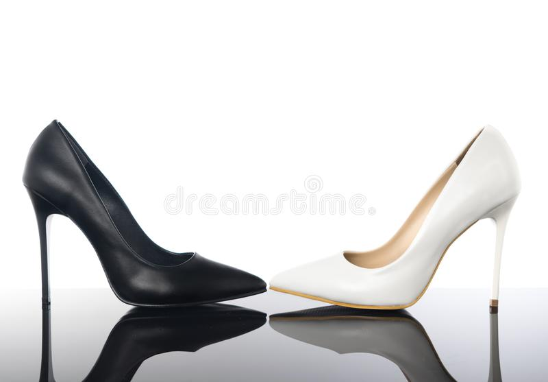 Black and white high heels pointed woman stiletto shoes on reflective floor. royalty free stock photos