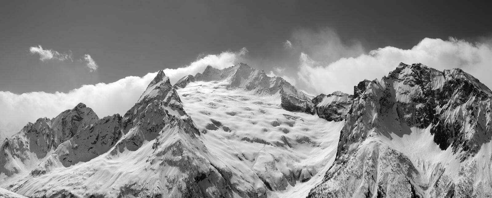 Black and white panorama of snowy glacier and mountain peak in fog. Caucasus Mountains at winter, region Dombay, view from ski slope stock photo