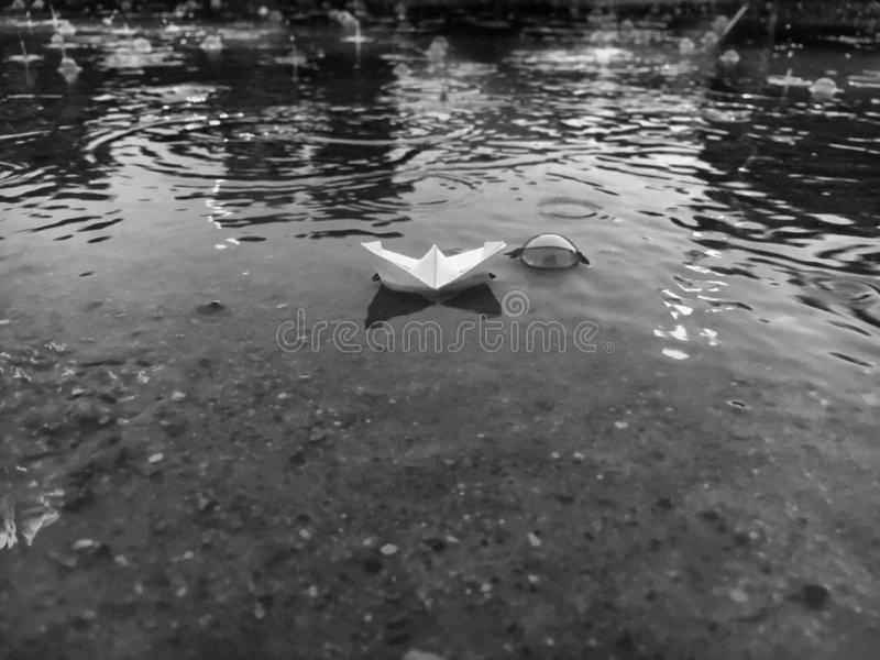 Black and white paper boat floating in a pond on rainy day. Small paper boat floating in a water puddle on a rainy day. Black and white lanscape stock image