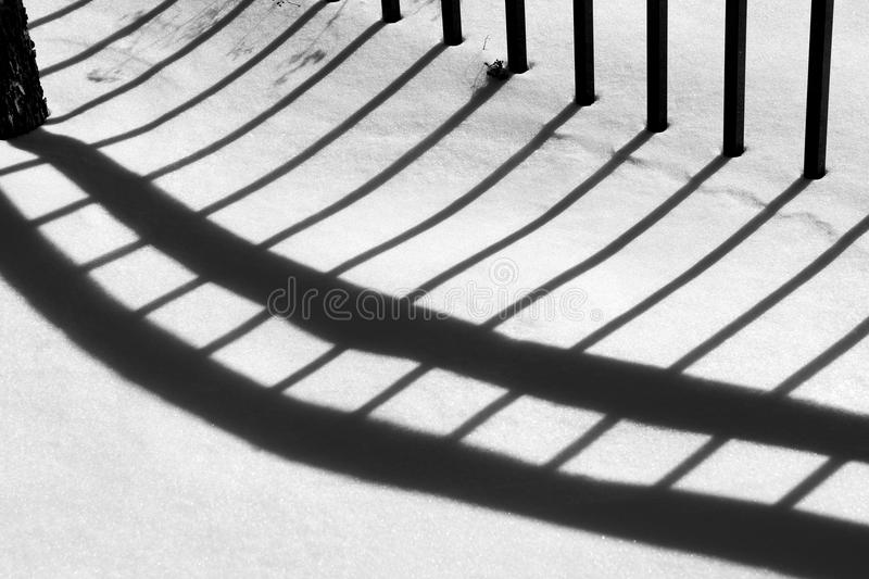 Black on white. In a park in Rosemont quarter in Montreal, fence and its shadow stock photography