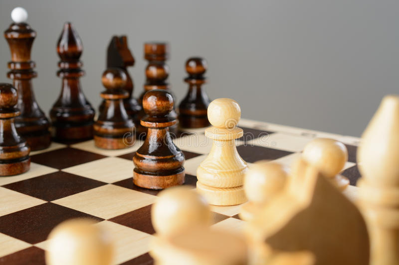 Black and white pawns facing each other. On a chessboard royalty free stock photo