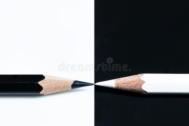 Black and a white pencils on a black and white surface - great for a cool background. A black and a white pencils on a black and white surface - great for a cool stock image