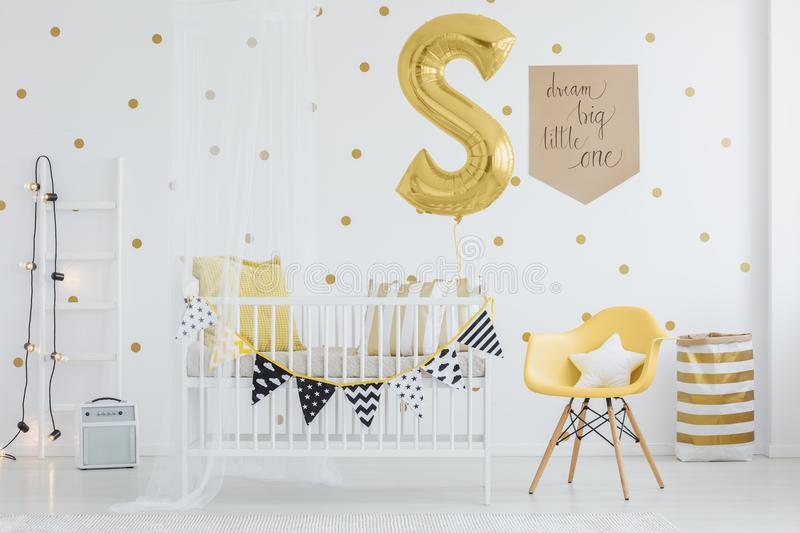 Pennants hanging on crib. Black and white pennants hanging on wooden crib in baby room with golden balloon, material basket and lamps on ladder royalty free stock images