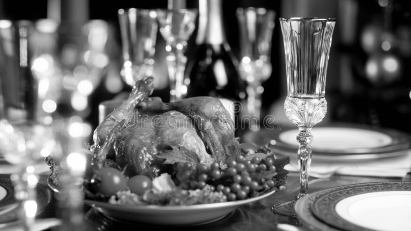 Black and white image of baked chicken on served festive dinner table royalty free stock photography