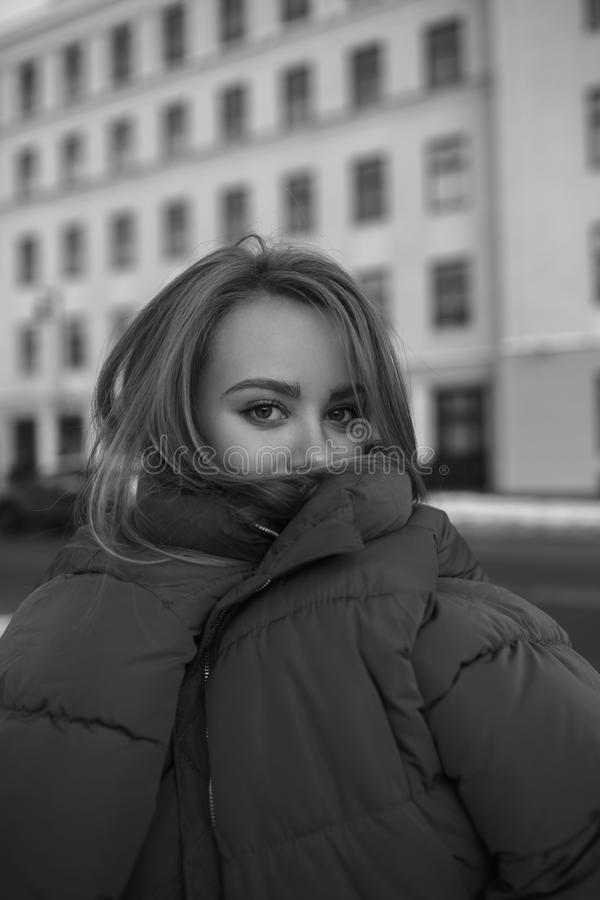 Black and white photo of beautiful funny girl in huge jacket stock image