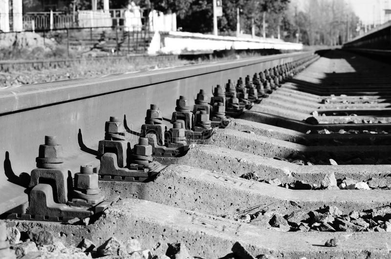 Black and white photo bolts that secure the rails to the sleepers on the railway direction. Black and white photo bolts that secure the rails to the sleepers on royalty free stock photo