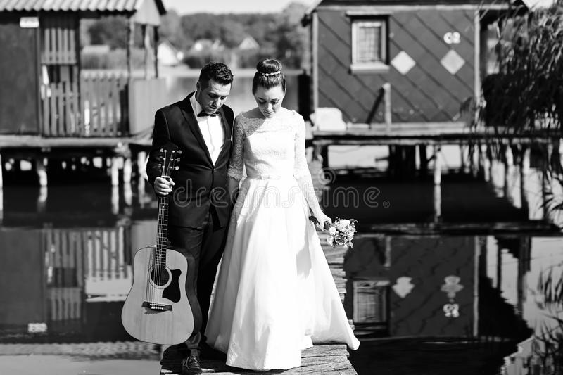 Black and white photo of bride and groom near lake stock photography