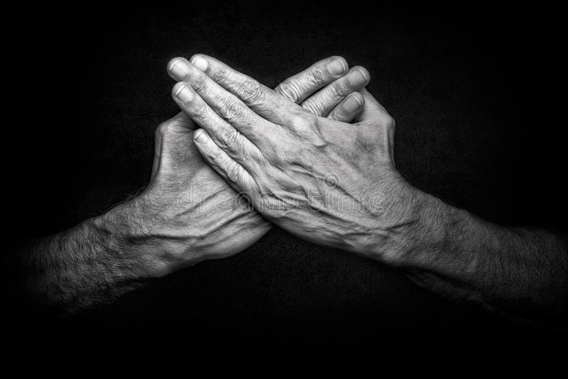 Crossed man`s hands. Black and White photo of crossed man`s hands on dark background, symbolizing protection of security royalty free stock images