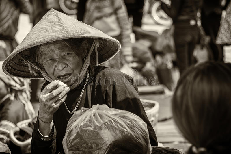 Black and white photo of an elderly woman at market. Senior female with conical eating snack at the rural open market of Sapa Vietnam stock image