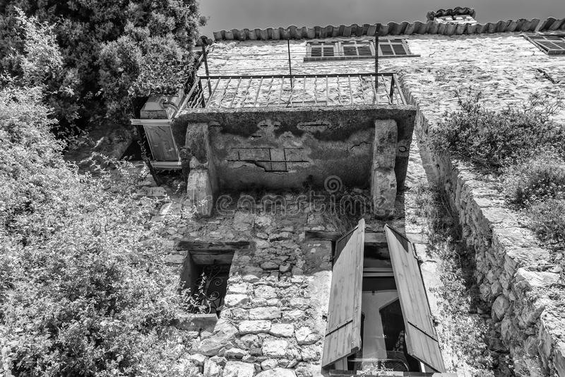Black and white photo of the facade of an old house in a narrow street in the old center of the  picturesque medieval village of royalty free stock photos