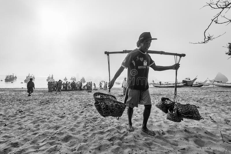 Black and white photo of fisherman bring his catch to shore royalty free stock photo