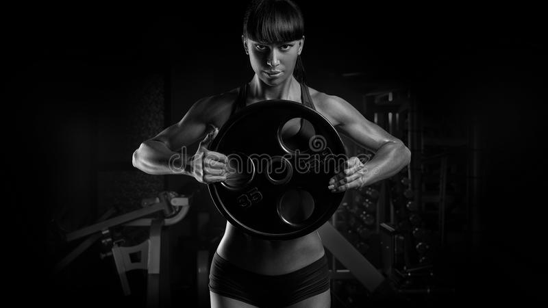Black and white photo of fit power athletic confident young woman bodybuilder doing exercises with heavy weight barbell plate in stock images