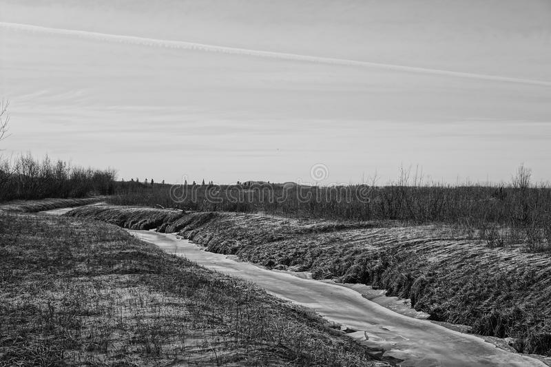Black and white photo of frozen creek. Black and white photo of a frozen creek royalty free stock photography