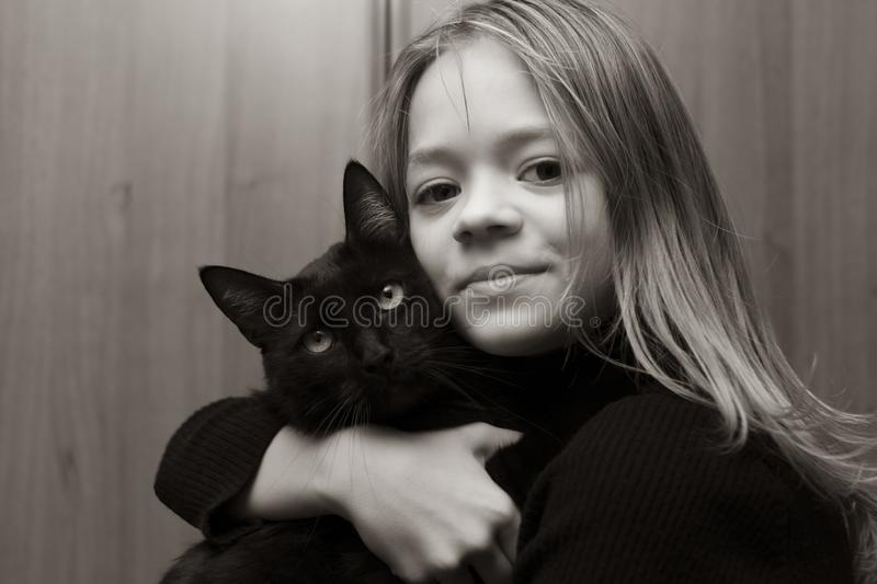 Black and white photo of a girl with a cat. Black and white photo of a girl with a black cat at home stock photos
