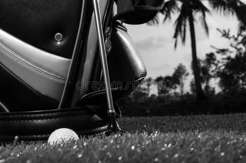 Black and white photo of golf clubs and a golf ball in low light royalty free stock photo