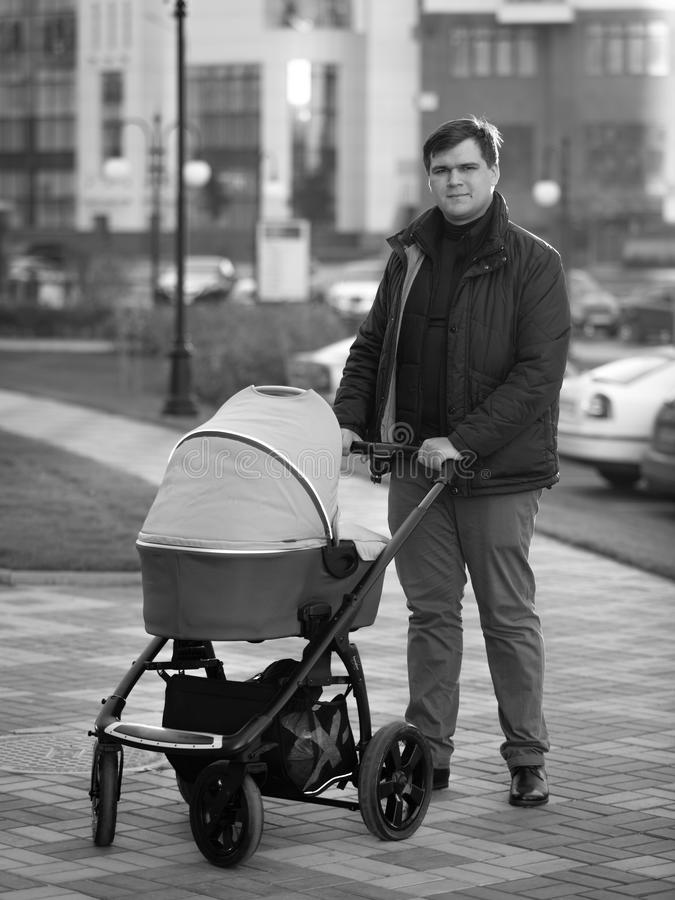 Black and white photo of happy father walking with baby in pram stock images