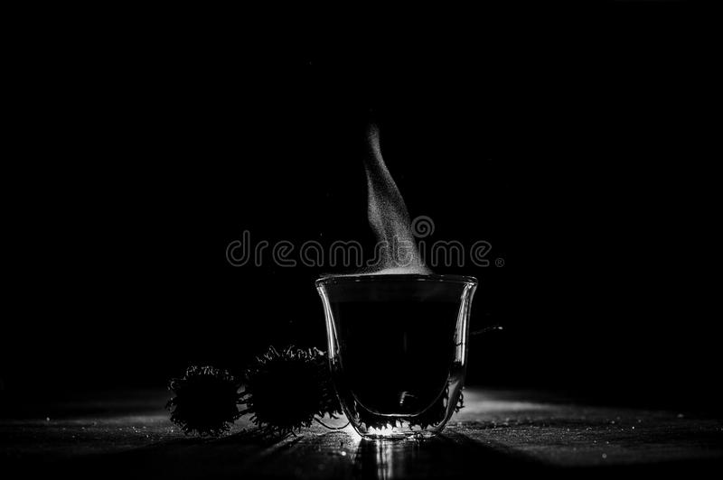 Black and white photo of a hot cup of coffee with steam. Located on the table. Coffee concept stock images