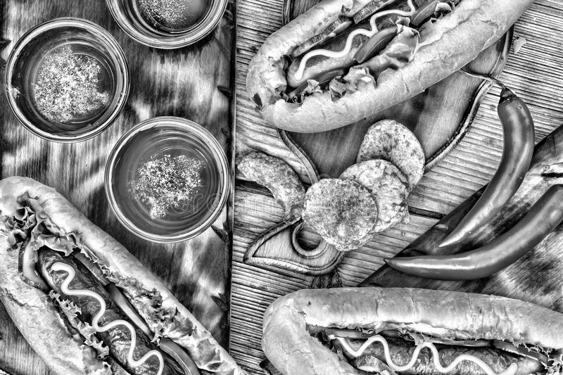Black and white photo. Hot dogs, beer, chips on wooden table in the pub. Top veiw royalty free stock photos