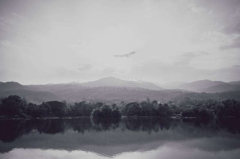 Black and white photo of lake with mist in fall.  stock photos