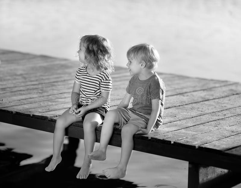 Black and white photo of little boy and girl sitting on wharf wooden in summer day. Romantic concept stock images