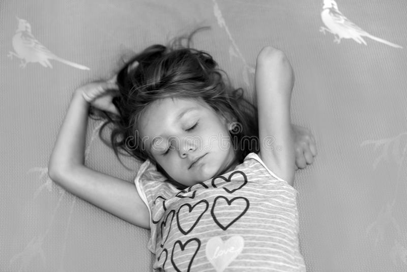 A black and white photo of a little girl sleeping in a bed stock images