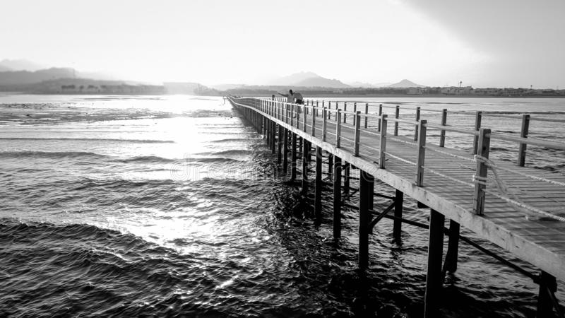Black and white image of long wooden pier in the ocean. Calm sea waves and amazing sunset over the mountains stock photos