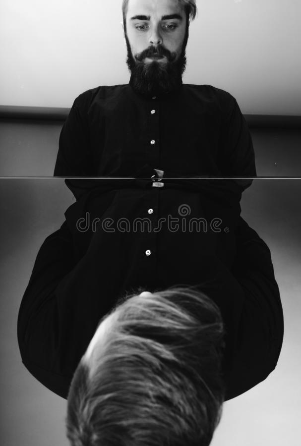 Black and white photo of a man with a beard and stylish hairdo dressed in the black shirt standing over the mirror with stock photo