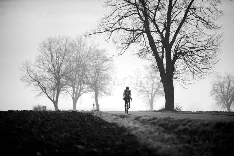 Black and white photo of a man gravel bike. Cyclist on the empty road and the trees in the mist royalty free stock photo