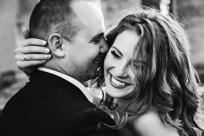 Black and white photo of man kissing his laughing woman royalty free stock photo
