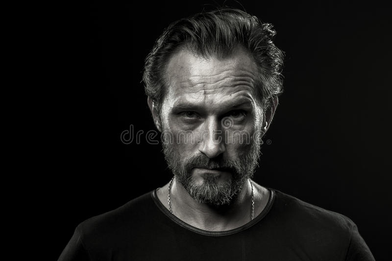 Black and white photo of mid aged man showing severe emotion. Beardy male in black t-shirt on dark background with serious look royalty free stock photo