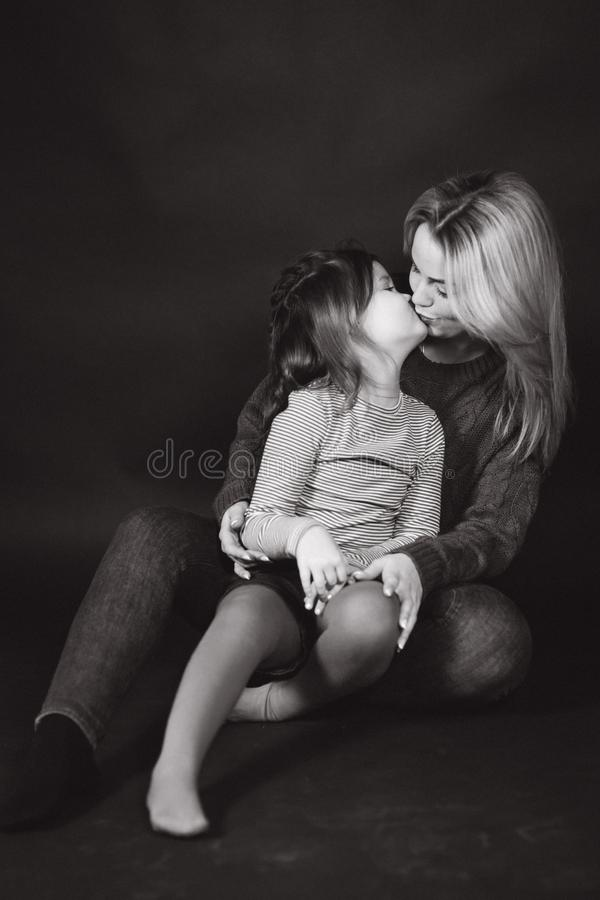 Black and white photo of mom and daughter in studio. Balck background.  royalty free stock image