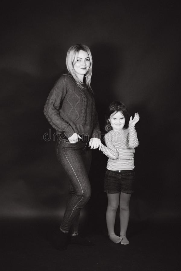 Black and white photo of mom and daughter in studio. Balck background.  stock images