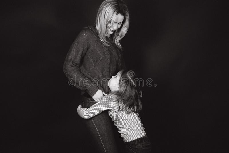 Black and white photo of mom and daughter in studio. Balck background.  royalty free stock photo