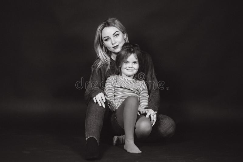 Black and white photo of mom and daughter in studio. Balck background.  royalty free stock images