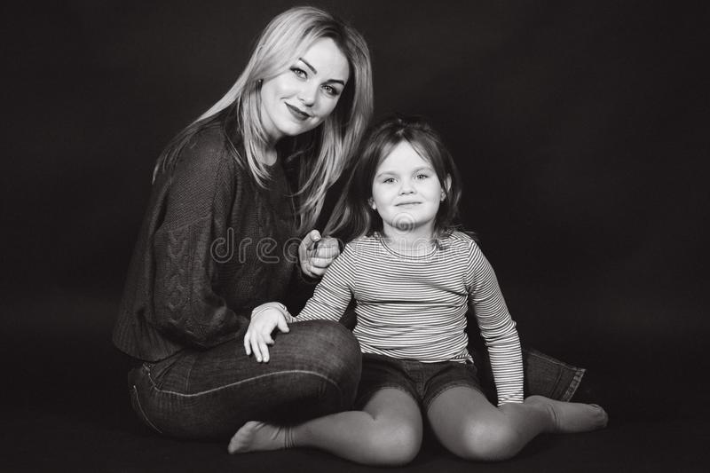 Black and white photo of mom and daughter in studio. Balck background.  stock image