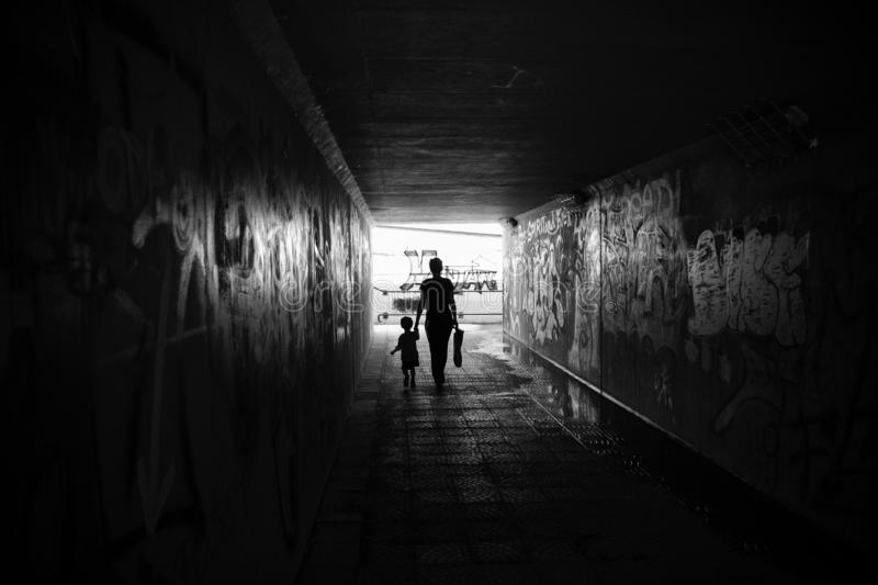Black and white photo of mother with baby in underpass with graffiti stock image