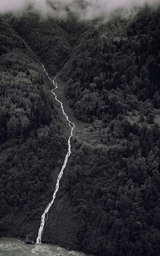 Black and white photo of a mountain river flowing down the gorge on the background of verdant mountains and clouds. Georgia royalty free stock photography