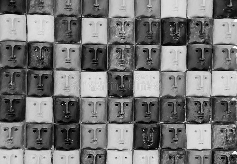 Black and white photo of multiple faces. Multiple faces with the same expression. Black and white photo stock image