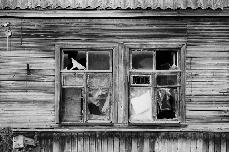 Black and white photo old wooden village abandoned house with broken glass in windows, Russia. Black and white photo old wooden village abandoned house with stock images
