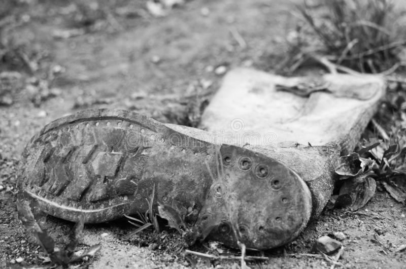 Old worn discarded left boot. Roadside trash close up. Black and white photo stock photography