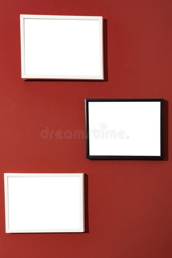 Black and white photo picture frames white, blank painting frames on red wall. Mock Up stock photography