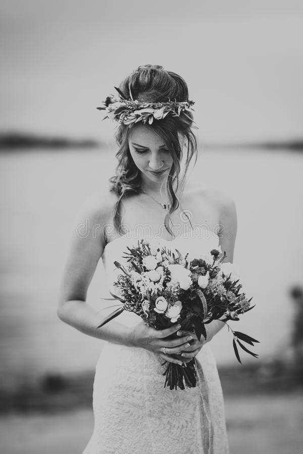 Black white photo portrait of the bride against the background of the river.  royalty free stock image