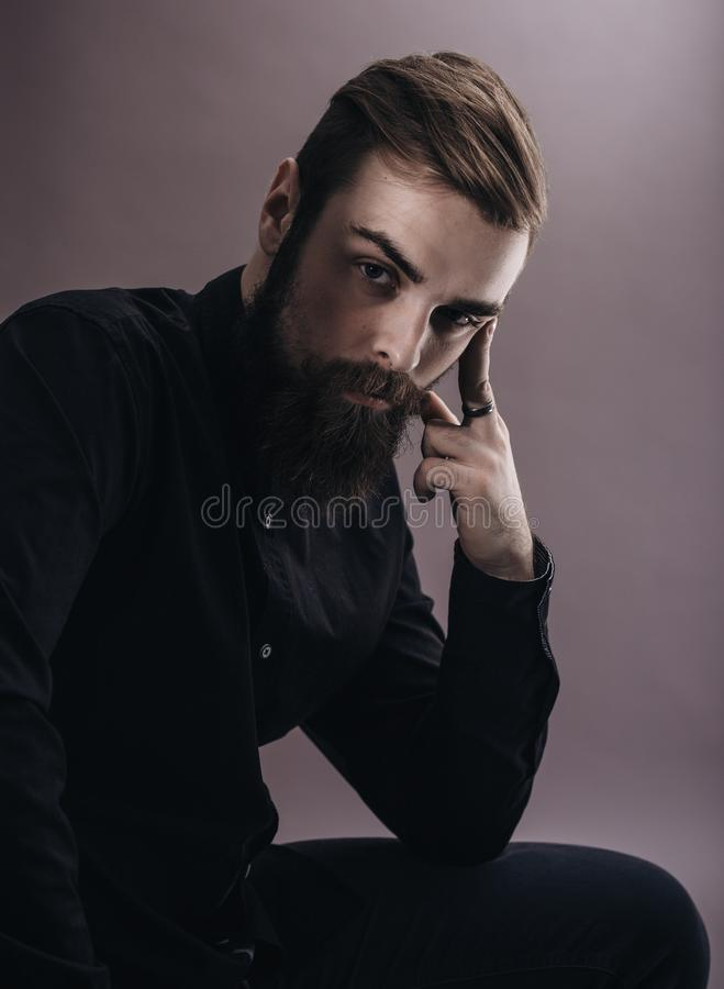 Black and white photo portrait of a pensive man with a beard dressed in the black shirt on the white background stock image